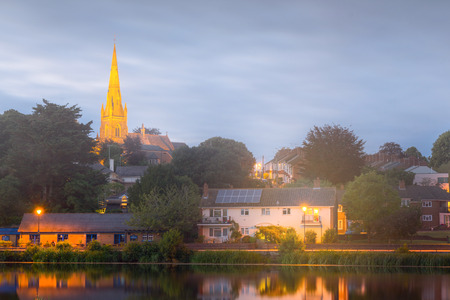 Small houses on the river bank in the city of Exeter. In the background stands the church of St. Leonard. Devon. UK