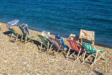 Wooden deck chairs on a pebble beach at the waters edge. Beer. UK Stock Photo