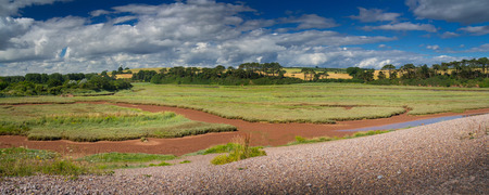 Panorama of a picturesque place on the shore of an English channel - Budleigh Salterton. Sunny summer day. Clouds in the blue sky. Devon. England