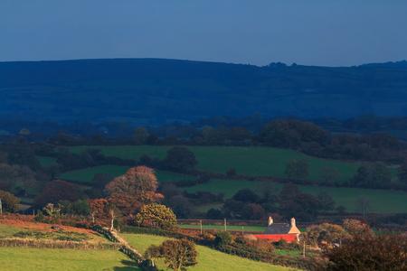 Scenic view of the Dartmoor hills. Low autumn sun illuminates a lonely house. Devon UK