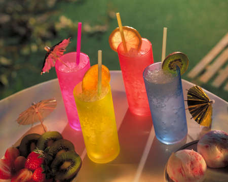 COCKTAIL DRINKS ON TABLE WITH STRAWS COCKTAIL UMBRELLAS AND FRUIT