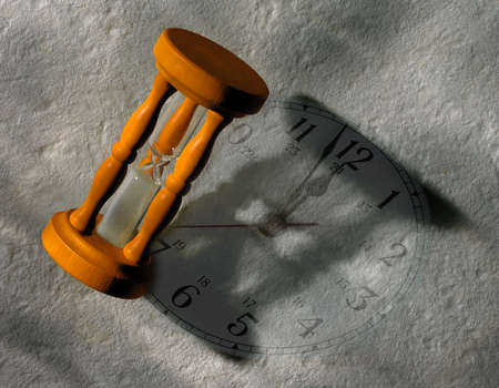EGG TIMER CASTING SHADOW ON GREY CLOCK FACE Stock Photo
