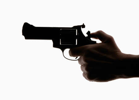 HAND HOLDING REVOLVER IN SILHOUETTE ON WHITE BACKGROUND