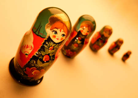 FIVE RED AND GREEN PAINTED RUSSIAN DOLLS ON YELLOW BACKGROUND