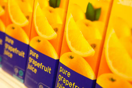 Cartons of grapefruit juice on supermarket shelf in close up