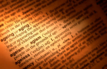 Close up of dictionary page showing definition of the terms ageing ageism Banco de Imagens