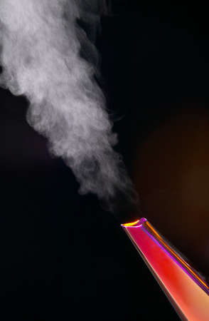 Steam flowing from spout of boiling kettle on black background