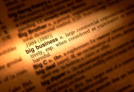 Close up of dictionary page showing definition of the term big business Фото со стока