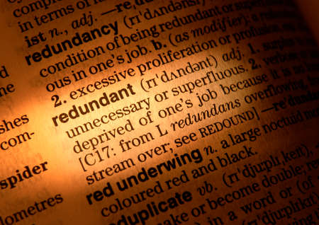 Close up of dictionary page showing definition of the word redundant