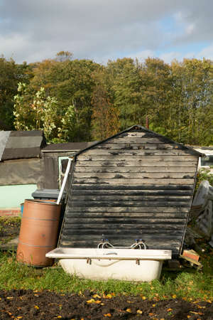 Leaning shed and old bath in garden allotment