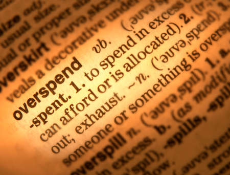 Close up of dictionary page showing definition of the word overspend Banco de Imagens