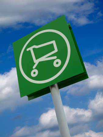 Rectangular sign with painted white icon of supermarket trolly isolated on blue sky and cloud background Фото со стока