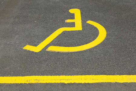 Painted icon of wheelchair user in disabled parking space