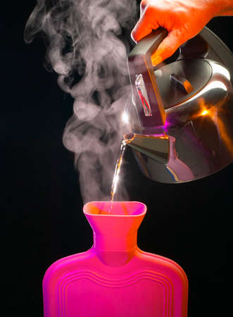 Boiling water from kettle pouring into hot water bottle on black background