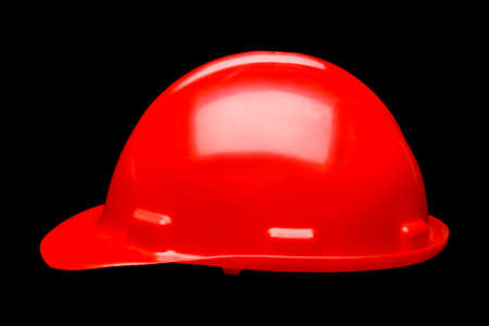 Red hard hat safety helmet isolated on black background