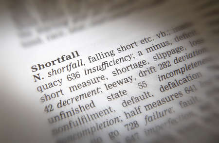 Close up of dictionary page showing definition of the word shortfall