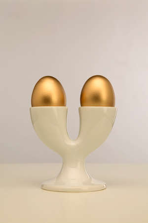 Two golden eggs in double white egg cup