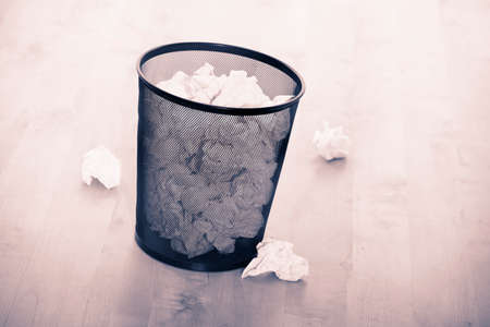 Waste bin full of crumpled paper on wooden floor Фото со стока
