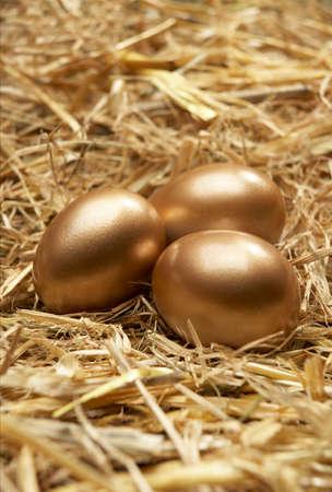 Three golden eggs on nest of straw