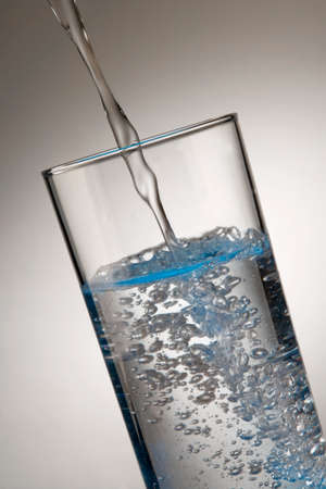 Water pouring into glass tumbler in close up