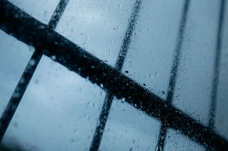 Rain drops on glass window pane with security bars