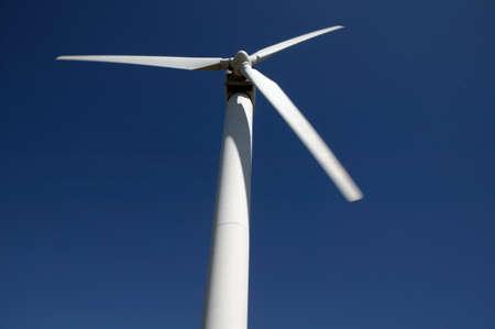 Single wind turbine against blue sky