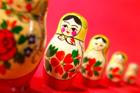 Russian dolls in a line on red background Фото со стока