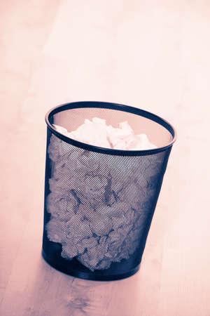 Waste paper bin full on crumpled paper on wooden floor