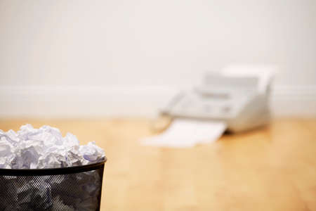 Waste paper bin full of crumpled paper with old fax machine in background