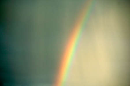 Rainbow in stormy sky with slanting rain Фото со стока