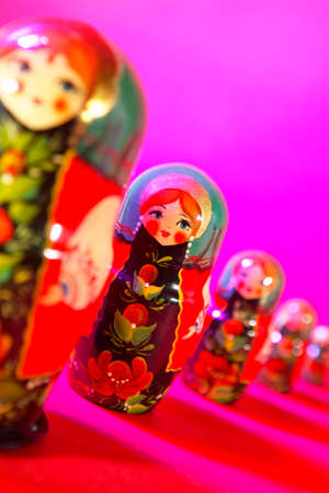 Russian dolls in a line on pink and red background Stockfoto