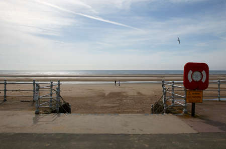 One man taking picture of another man on Blackpool beach, England