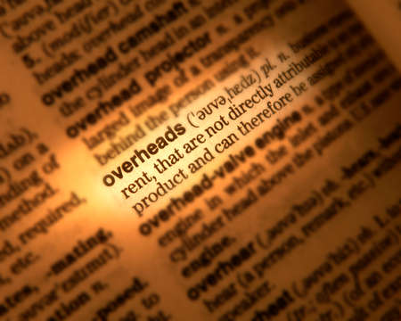 Close up of dictionary page showing definition of the word overheads Фото со стока