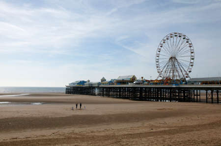 Blackpool beach and north pier with ferris wheel in background Редакционное