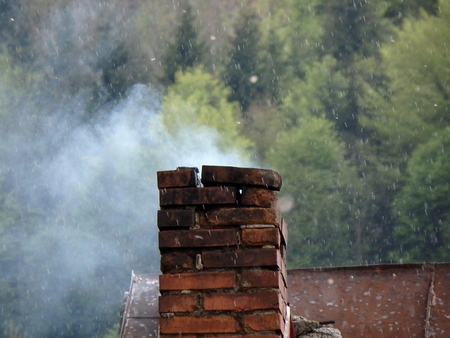 cement chimney: Smoke rises from an old chimney, old chimnery