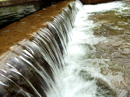 Small waterfall, artificial cascade on the river,