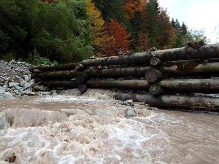 Houten dam op een bergrivier, traditionele structuur voor drijvend hout, Stockfoto - 87974799