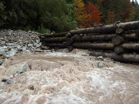 Houten dam op een bergrivier, traditionele structuur voor drijvend hout,