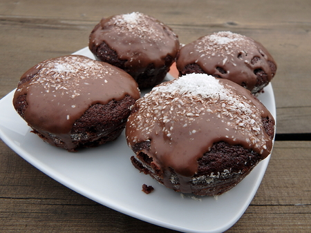 Delicious homemade muffin with chocolate and grated coconut on a plate Stock Photo