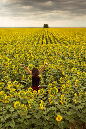 vastness: Beautiful young woman in a field of flowers having a joyful and positive attitude Stock Photo
