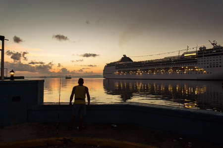 Man fishing at sunrise in Havana port with a cruise ship in background, Cuba.