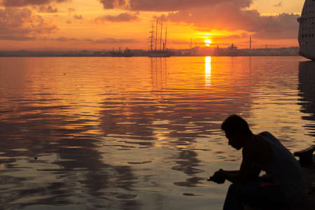 Silhouette of man fishing by hand and sail boat at sunrise in Havana port, Cuba