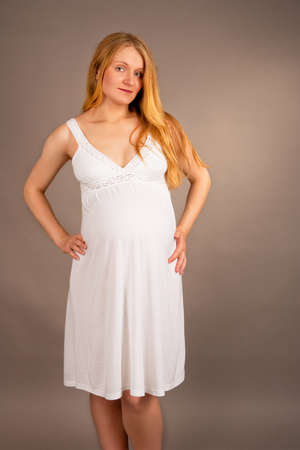charming blonde pregnant woman in white nightshirt isolated Stock Photo