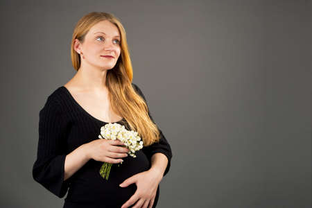 beautiful young pregnant blonde woman with flowers isolated photo