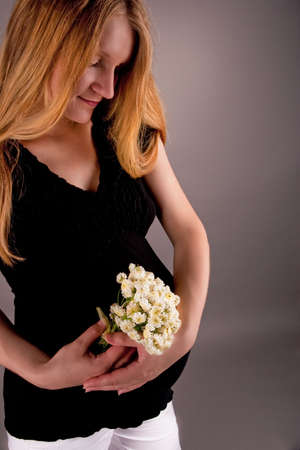 pretty young pregnant blonde with flowers Stock Photo - 5754566