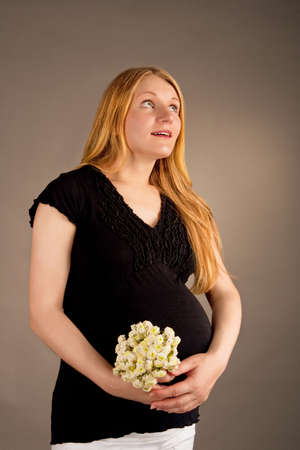 surprised young pregnant blonde with flowers Stock Photo - 5754562