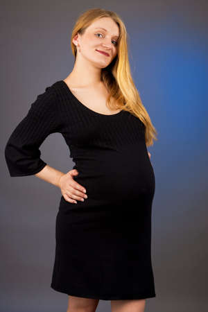 smiling young pregnant blonde in black dress isolated
