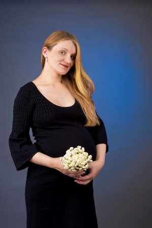 positiveness: bastante joven rubia embarazada con flores Foto de archivo