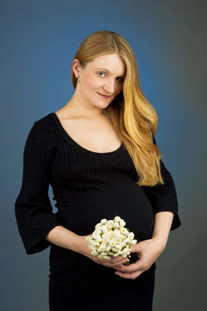 pretty young pregnant blonde with flowers