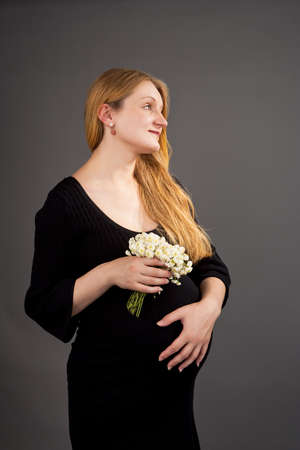head tilted forward: pretty young pregnant blonde with flowers